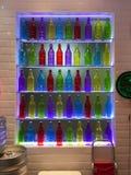 Bottiglie variopinte sullo scaffale di vetro fotografia stock