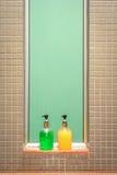 Bottiglie verdi e gialle di sapone e di sciampo contro vetro verde e la parete piastrellata Fotografia Stock