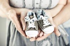 Bottini appena nati del bambino in mani dei genitori Fotografie Stock