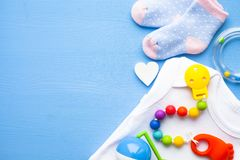 Bottini gialli del bambino Le scarpe ed i giocattoli dei bambini su fondo blu Neonato fotografia stock