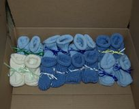 Bottini tricottati del bambino del ragazzo con i nastri allineati in una fila - colori: Blu-chiaro, blu scuro, bianco fotografia stock libera da diritti