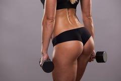 Bottino atletico della ragazza con le teste di legno isolate su fondo grigio con copyspace Fotografie Stock Libere da Diritti