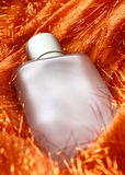 Bottle. Perfume bottle on fancy orange tassels color fabric royalty free stock image