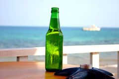 The bottle. Of beer on the table next to the beach stock photos