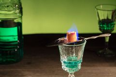 Absinthe. Bottle of absinthe and glasses with burning cube brown sugar royalty free stock photography