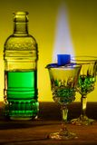 Bottle of absinthe and glasses with burning cube brown sugar.  stock photography