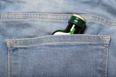 Bottle with alcohol in back pocket of blue jeans Royalty Free Stock Photography