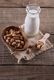 Bottle of almond milk and nuts over rustic wooden background Stock Photos