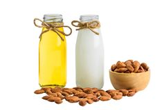 Bottle of almond milk and oil with Peeled almonds in wooden bowl Stock Image