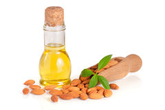 Bottle of almond oil and almonds with leaf in a wooden scoop iso. Lated on white background stock photos
