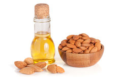 Bottle of almond oil and almonds in a wooden bowl isolated on white background Royalty Free Stock Photography