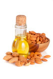 Bottle of almond oil and almonds in a wooden bowl isolated on white background.  Stock Photo