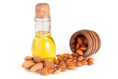 Bottle of almond oil and almonds in a wooden bowl isolated on white background.  Royalty Free Stock Images