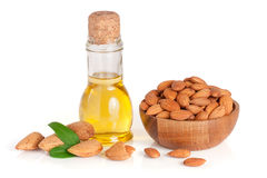 Bottle of almond oil and almonds in a wooden bowl isolated on white background.  Stock Images