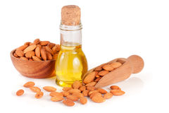 Bottle of almond oil and almonds in a wooden bowl and scoop isolated on white background.  Royalty Free Stock Images