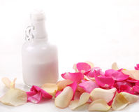 Bottle And Rose Petals Stock Photos