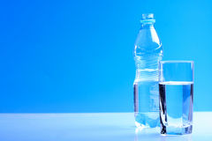 Bottle ang glass of water on blue background Stock Images