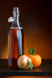 Bottle of apple cider. With ripe apples on rustic wooden table still-life Stock Images