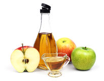 Bottle of Apple cider vinegar and apples. The open transparent full bottle and cup of Apple cider vinegar and a few different varieties of apples isolated on a stock image