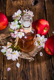 A bottle of apple cider vinegar (cider), fresh apples and apple-tree flowers on a wooden background. royalty free stock photos