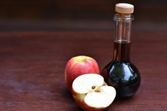 Bottle of apple cider vinegar next to ripe apples. royalty free stock photography
