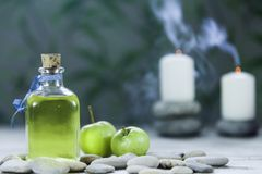 Bottle of apple oil massage, river pebbles, two small green apples and two candles with smoke on wooden table and herbal. Background royalty free stock photos