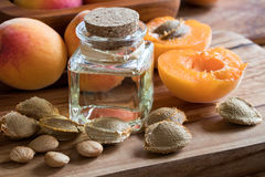A bottle of apricot kernel oil with apricot kernels and apricots. A bottle of apricot kernel oil with apricot kernels and ripe apricots on a wooden background stock photo