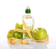 Bottle with aqua, apple grapes, and measure Stock Photo