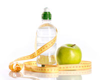 Bottle with aqua, apple and measure Stock Images