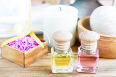 Bottle of aroma essential oil with flower on wooden table. Royalty Free Stock Image