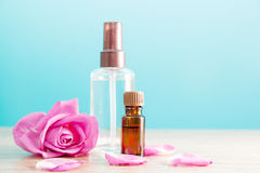 Bottle with aromatic oil and pink rose Stock Image