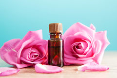 Bottle with aromatic oil and pink rose Stock Images