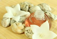 Bottle of aromatic oil, stones, flowers. Royalty Free Stock Photo
