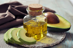 Bottle of avocado essential oil. With fresh avocado fruit closeup
