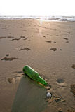 Bottle on a Beach. Green bottle in te sand on a beach stock images