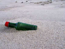 Bottle at the beach. Bottle washed ashore to the beach. Wind completely sandblasted the glass stock images