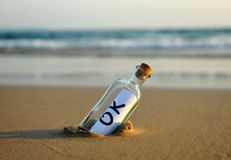 Bottle on the beach with an affirmative answer inside, okey Royalty Free Stock Photography