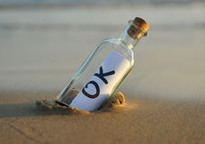 Bottle on the beach with an affirmative answer inside, okey Royalty Free Stock Image