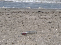 Stranded bottle at the beach. An empty bottle laying on the beach Stock Photo