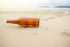 Bottle on beach sea and sky.from the sea rinsed bottle on the beach. royalty free stock images
