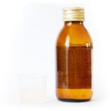 Bottle and beaker with medicine Royalty Free Stock Image