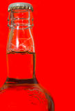 Bottle of beer. Set against a red background stock photo