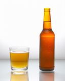Bottle with beer 2. Bottle with beer and a glass filled with beer with foam on a white reflecting surface Stock Images