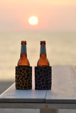 Bottle of beer on the beach at sunset Royalty Free Stock Image