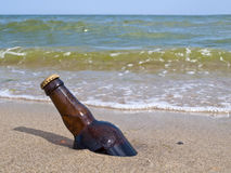 The bottle of beer is buried in sand Royalty Free Stock Images