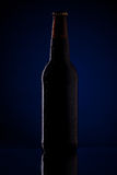 Bottle of beer with drops. On dark blue background Royalty Free Stock Photography