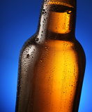 Bottle of beer with drops on a blue. Royalty Free Stock Photo