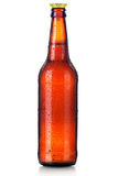 Bottle of beer with drops isolated on white Royalty Free Stock Images