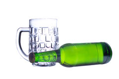 A bottle of beer and an empty beer mug Stock Images
