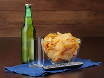 Bottle of beer, empty glass and bowl with chips Stock Photography